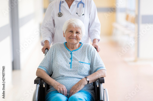 Senior woman in wheelchair with doctor in hospital