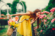 A Cute And Stylish Girl In A Yellow Dress And Long Hair Rides On A Bicycle With A Basket Of Flowers In The Sunny Summer Garden