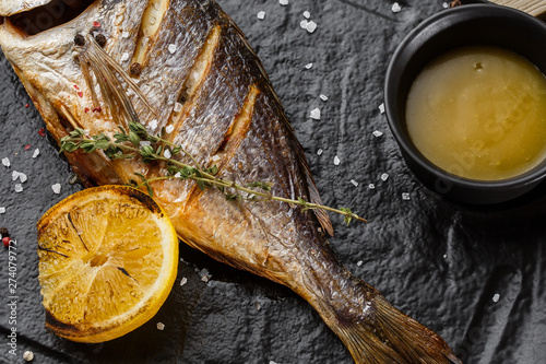 Fototapeta  Delicious grilled dorado or sea bream fish with lemon slices, spices, rosemary on dark stone