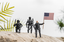Selective Focus Of Toy Soldiers Holding American Flag On Sand Hill