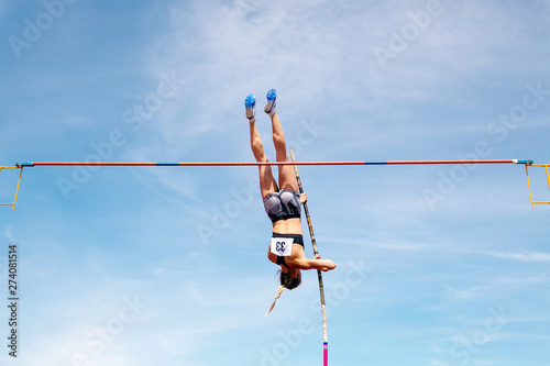 Vászonkép pole vault woman jumper on blue sky background in athletics