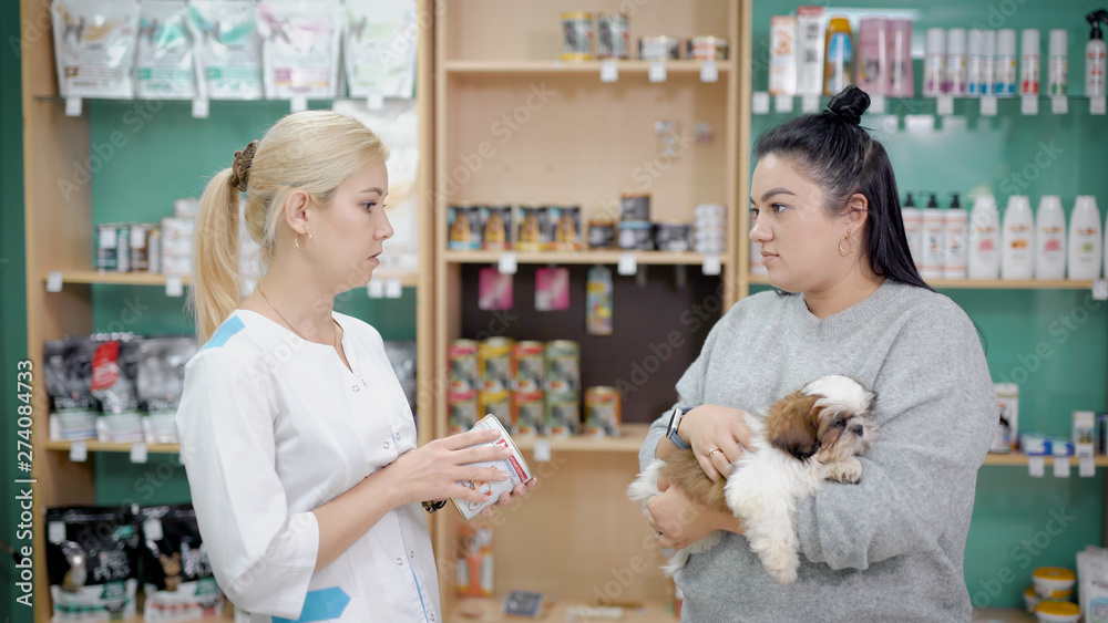 Fototapety, obrazy: Woman talking to a saleswoman in a vet store for pets, buying pills and food for sick dog.