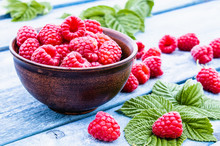 Ripe Red Raspberries On A Bowl Against The Background Of Blue Boards. Selective Focus.
