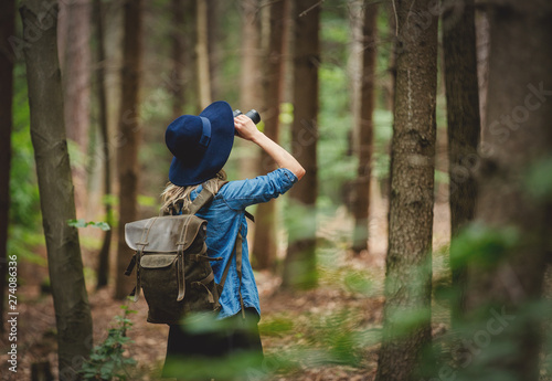 Canvastavla Young woman with binocular and backpack in a forest