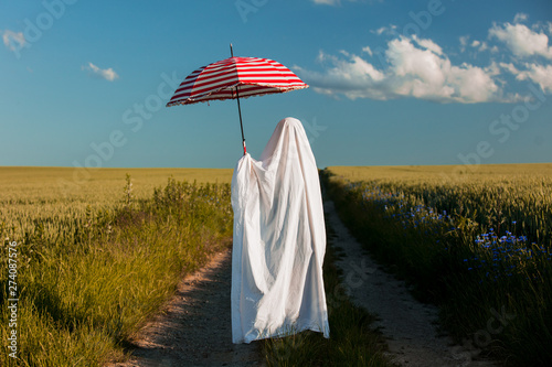 Foto auf Gartenposter Blau Jeans cute ghost in a bed sheet with umbrella on countryside road near a wheat field