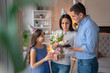 Happy family celebrating mother's birthday. Man standing with holiday cake in hand, little girl with present box for her mother with flowers in her hands