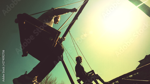 Two girls swinging on rope swing against sunrise sun  vintage