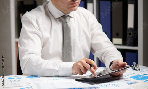 Fototapety, obrazy: Businessman working with tablet pc, calculating, reading and writing reports. Office employee, table closeup. Business financial accounting concept.