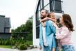 Leinwandbild Motiv happy man piggybacking daughter near cheerful wife and house
