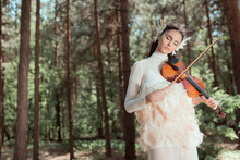 Dreamy Woman In White Swan Costume Standing On Forest Background, Playing On Violin