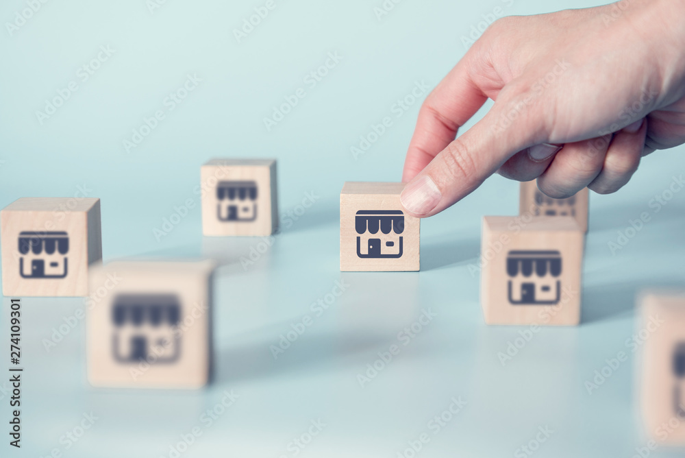 Fototapety, obrazy: Woman hand choose wood blog with franchise icon on blue background. Franchise business concept.