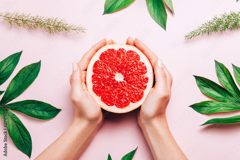 Fototapety, obrazy: Female's hands holding grapefruit on pink background with tropic plants and leaves.