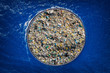 Concept cleaning ocean water from debris and plastic. Removing contaminants using ship and grid