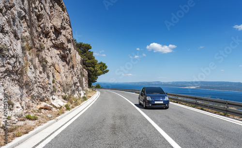 Poster Montagne Car rushes along the road to the sea. Car highway along the coast of the Adriatic Sea, in Brela, Croatia.