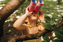 Closeup Portrait Of Little Girl Looking Through A Binoculars Searching For An Imagination Or Exploration In Summer Day In Park. Child Playing With Binocular Pretend Safari Game Outdoors In The Forest