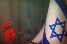 Israel Flag For Honour Of Veterans Day Or Memorial Day With Two Red Carnation Flowers Mockup. Glory To The Israel Heroes Of War Concept On Light Blue Blurred Natural Wood Wall. Background.