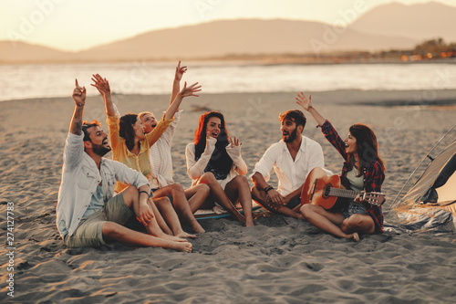 Happy friends sitting on the beach singing and playing guitar during the sunset - 274127783