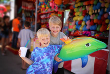 Two Happy Children With Toy Prizes At Small Town American Carnival