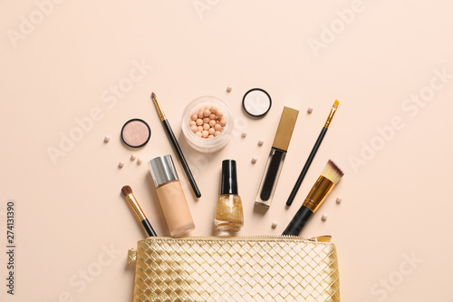 Fototapeta Cosmetic bag and different luxury makeup products on color background, flat lay obraz