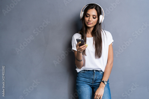 Smiling woman listening music in headphones and using smartphone over gray background. - 274132382