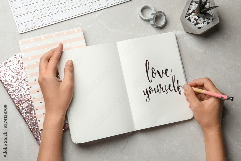 Fototapeta Woman writing LOVE YOURSELF in journal on grey table, flat lay
