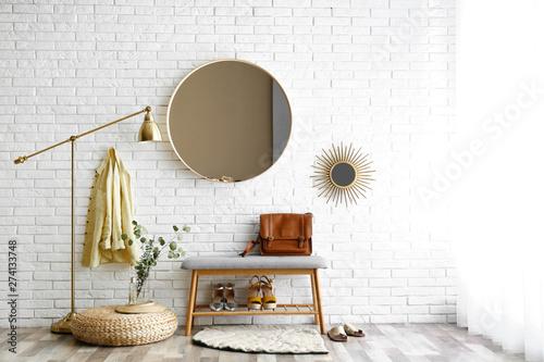 Obraz Hallway interior with big round mirror and shoe storage bench near brick wall - fototapety do salonu