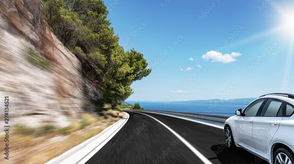 Fototapety, obrazy: White car rushes along the road to the sea. Motion blur effect.