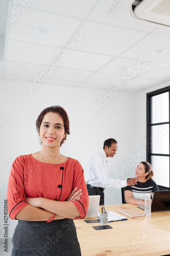 Portrait of young female leader standing with arms crossed and smiling at camera with business people working in the background