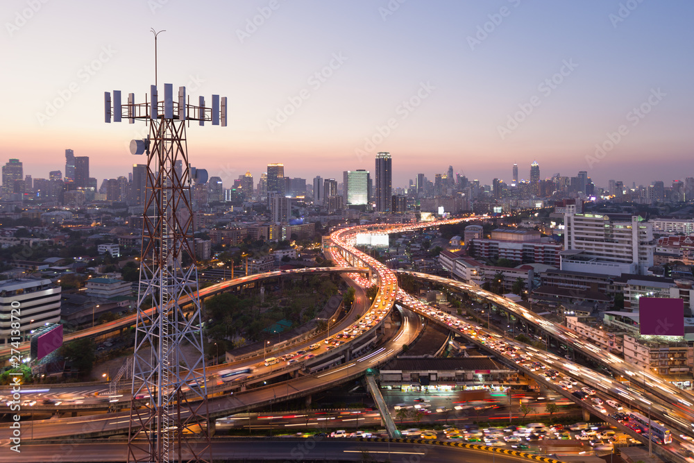 Fototapeta Telecommunication tower with 5G cellular network antenna on city background