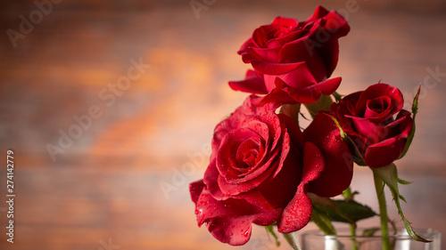 Red rose in vase on old wooden background, Vintage style