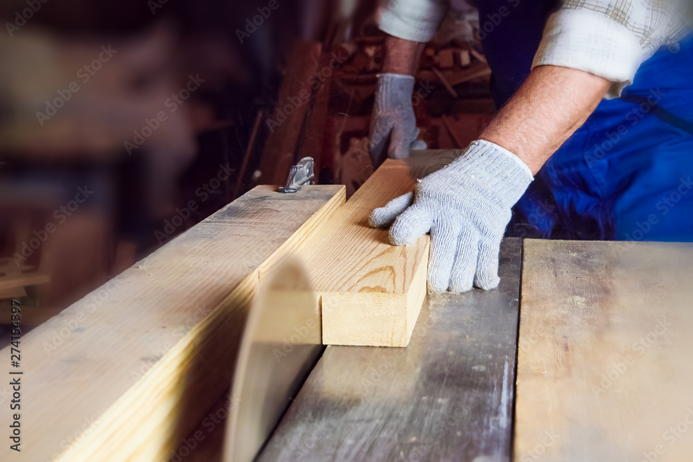 Fototapety, obrazy: Carpenter works on woodworking machines in the carpentry workshop. A man works with a tree