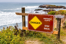"""Danger, Unstable Cliffs, Stay Back"" Sign Posted On The Pacific Ocean Coastline On An Area With Eroded Cliffs And Risk Of Landslide, California"