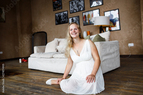 Fotografie, Obraz  Portrait of a beautiful long-haired pregnant blonde, gracefully sitting on floor
