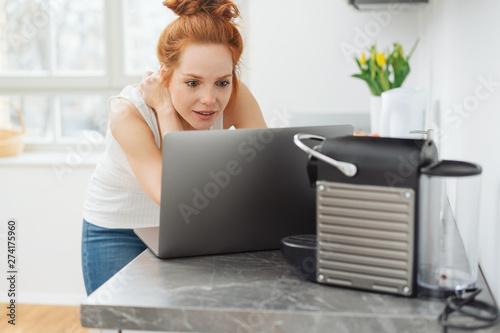 Foto  rothaarige frau steht in der küche und schaut auf den laptop