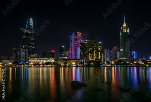 Poster The best of night view in Ho Chi Minh City, Vietnam. Colorful of city light beside the Saigon river with skyline at sunset. Royalty high quality free stock image.