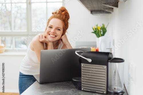 Fotografie, Obraz  lächelnde frau steht in ihrer küche mit ihrem laptop