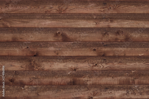 Old shabby wooden fence. Brown faded boards. Oak table, bars, logs. Wood surface. Abstract pattern texture background. Strips, stripes brown slats. Parallel bars.