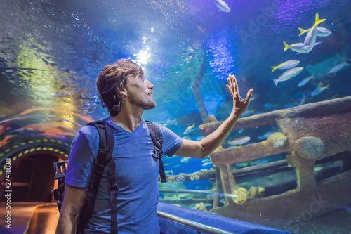 Photo curious tourist watching with interest on shark in oceanarium tunnel