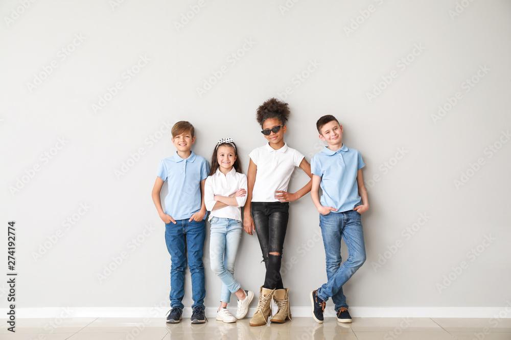 Fotografía  Stylish children in jeans near light wall