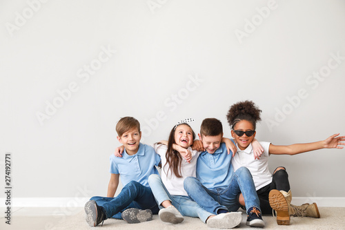 Fotomural Happy children in jeans sitting near light wall