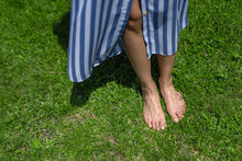 Young Woman With Bare Feet Standing On Green Grass