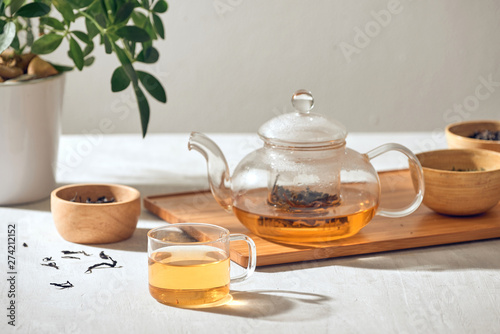 Cuadros en Lienzo Tea in a transparent cup and teapot on a wooden background