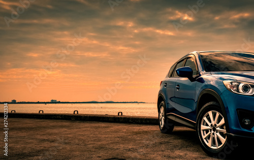 Fototapeta Blue compact SUV car with sport and modern design parked on concrete road by the sea at sunset in the evening. Hybrid and electric car technology concept. Car parking space. Automotive industry. obraz na płótnie