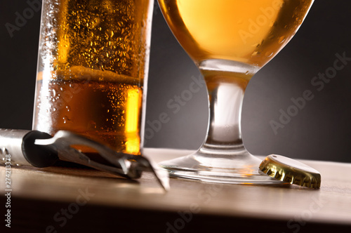 Poster Amsterdam Beer glass and bottle on table with bottle opener