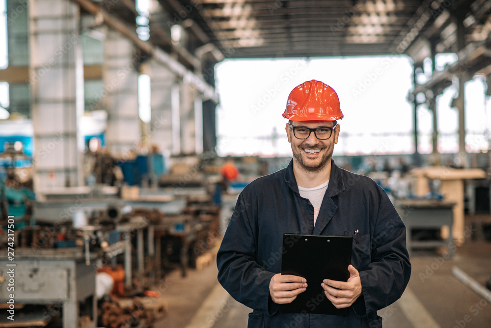 Fototapeta Portrait of a manual worker at large metal industry workshop.