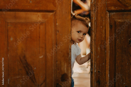 Cuadros en Lienzo  a pretty little girl hiding behind a large wooden door looking in the gap between them