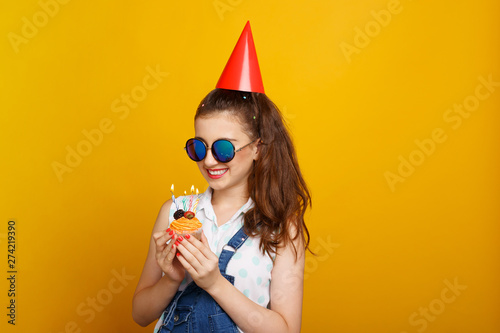Photo  Happy girl in sunglasses, over yellow background, holding in hands a cupcake with candles