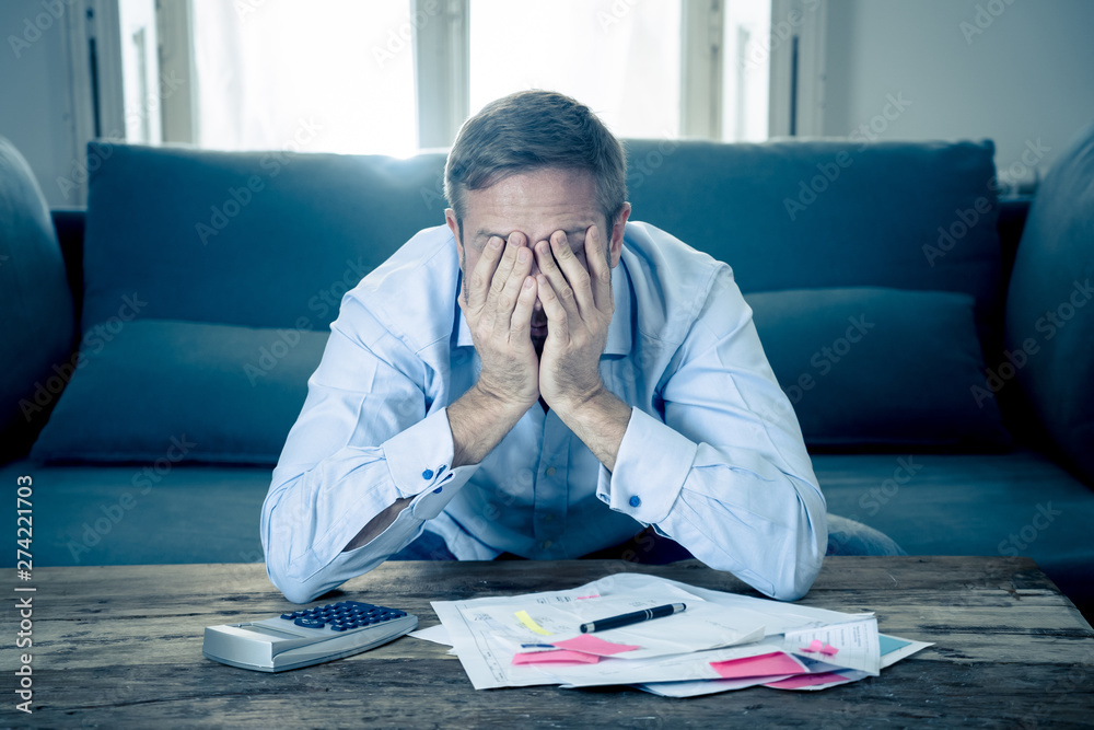 Fototapeta Upset man in stress paying bills counting finance with calculator bank papers expenses and payments