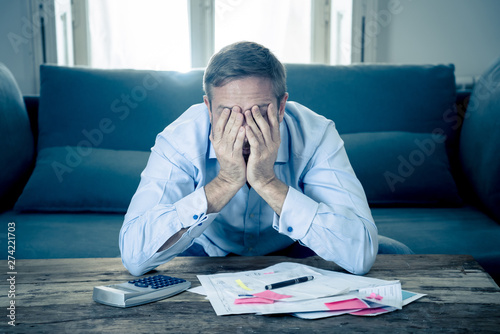 Obraz na plátně  Upset man in stress paying bills counting finance with calculator bank papers ex