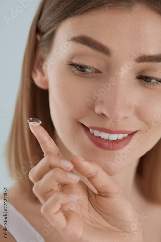 Eye care. Smiling woman with contact eye lens on finger closeup